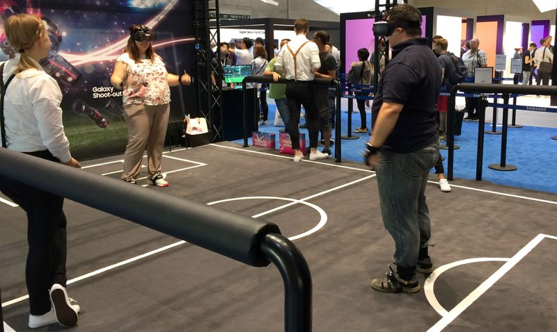 Man and woman playing Virtual Reality soccer at Samsung's booth in IFA Berlin 2018